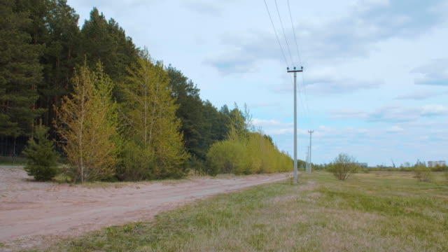 Rural landscape with country road, transmission line, field and green forest Rural landscape with country road, transmission line, field and green forest. Lockdown shot. Beautiful background with transmission line country road stock videos & royalty-free footage