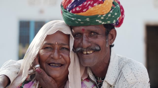 Rural lifestyle of a traditional family using technology and medical aid in Rajsthan Close-up portrait of a loving positive happy confident Indian elderly rural couple wearing traditional dress in Rajasthan, looking with joy and happiness at camera for photo video with toothy smiles sari stock videos & royalty-free footage