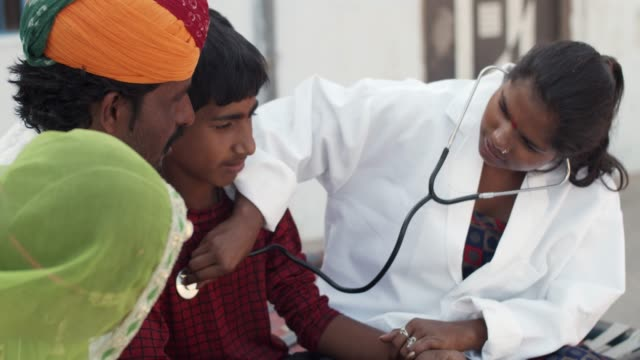 Rural lifestyle of a traditional family using technology and medical aid in Rajsthan Young medical inter female student using a stereoscope to check the heartbeat of teenage male child in rural Rajasthan, India with his father and mother concerned about his well being and health developing countries stock videos & royalty-free footage