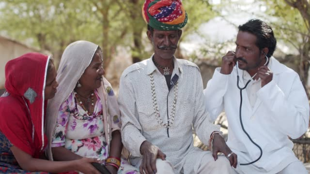 Rural lifestyle of a traditional family using technology and medical aid in Rajsthan Elderly parents, husband wife, along with their teenage daughter welcome namaste a male doctor to checkup medical consultant for their diseases and sufferings in knees of old age in rural India developing countries stock videos & royalty-free footage