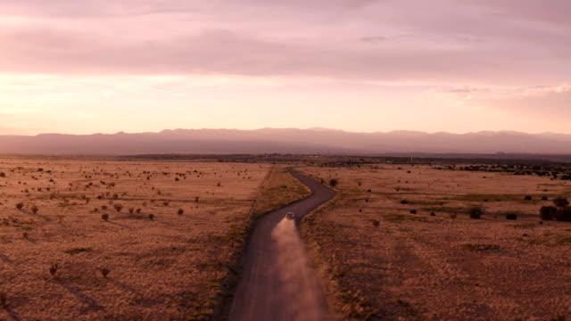 vídeos de stock, filmes e b-roll de cena rural da estrada do deserto de new mexico: carro que conduz no por do sol em uma estrada de terra - deserto
