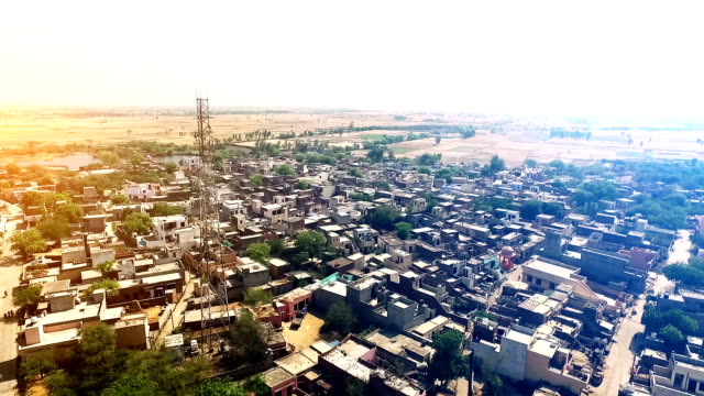 Rural village near pond Elevated view of rural village located in Haryana, India. developing countries stock videos & royalty-free footage