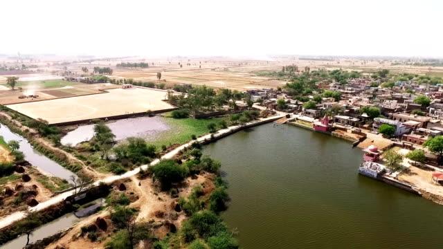 rural village near pond - харьяна стоковые видео и кадры b-roll