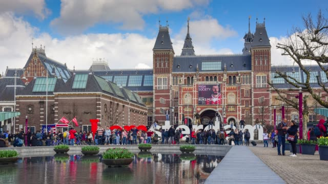 rush hour in amsterdam outside rijksmuseum; tourists walk on the street near sign - amsterdam video stock e b–roll