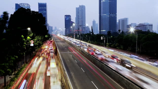 Rush hour traffic with modern buildings Time lapse of traffic jam with modern high rise buildings in Jakarta, Indonesia jakarta stock videos & royalty-free footage