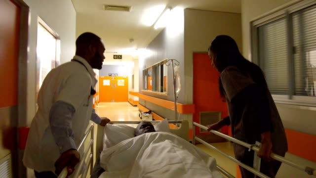 Rushing a patient to the Emergency room Doctors rushing a patient to the emergency ward hospital bed stock videos & royalty-free footage