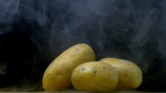 russet potatoes are on the table in cold, steam from frost in slow motion, copy space - patate video stock e b–roll