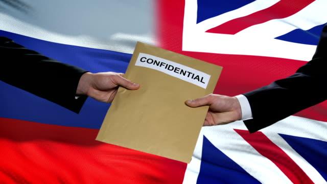 ロシアとgbの当局者は機密封筒を交換し、背景にフラグ - スパイ点の映像素材/bロール