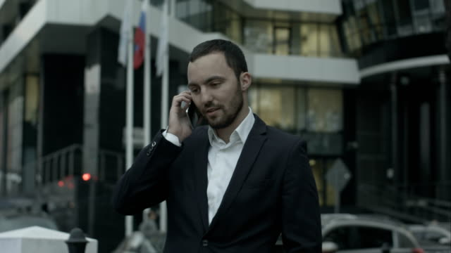 russian businessman answering call by phone and explain something to business partners, standing outside the office - lingua russa video stock e b–roll