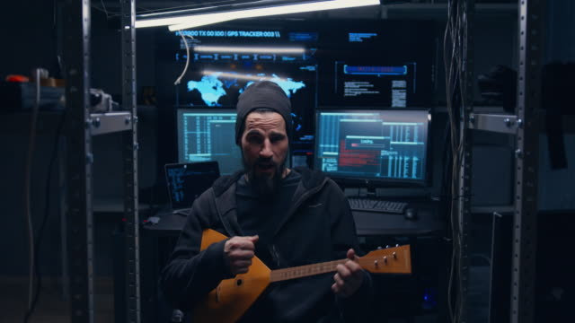 a russian hacker plays the balalaika after he managed to complete hacking of remote international servers and embed malicious code there. after a difficult job, he rests, rejoices and sings songs. - nazionalità russa video stock e b–roll