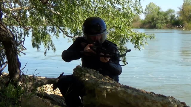 A Russian special forces soldier in an armor and a helmet settles on a position near the river bank and targets a crossbow. Marine recon video