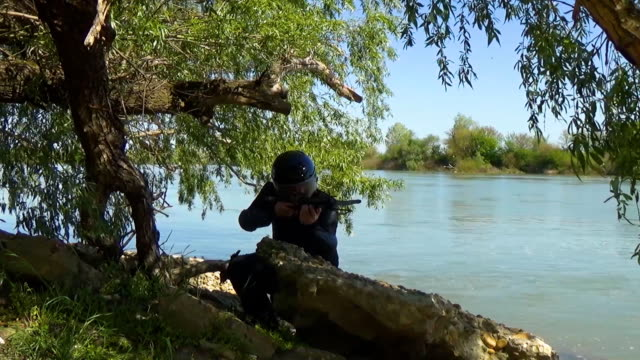 A Russian special forces soldier in an armor and helmet hides behind a stone on the river bank and targets a crossbow. Marine recon video