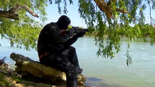 A Russian special forces soldier in armor and gloves, sitting on a rock near the shore of the lake and aiming from a crossbow. Marine recon video