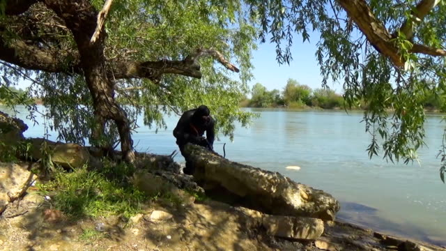 A Russian special forces soldier in armor goes to a position near the river bank and targets a crossbow. Marine recon video