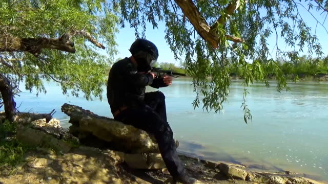 A Russian special forces soldier in the armor, closes the glass on his helmet and sits on a stone near the lake shore aiming from a crossbow. Marine recon video