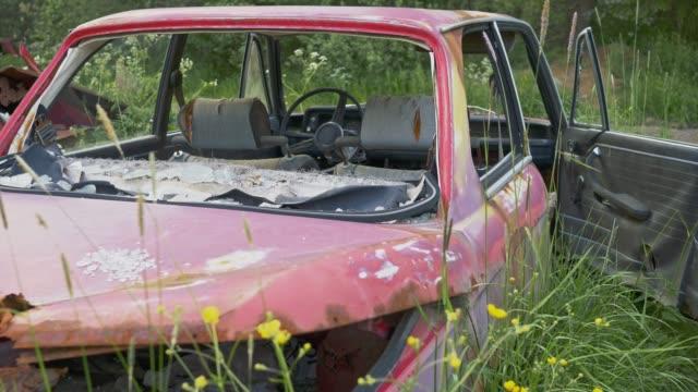 Rusty broken abandoned car on old cars junkyard cemetery. Gimbal shot, 4K