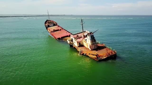 Rusty cargo shipwreck in advanced state of degradation stranded on shallow waters near the shore of Sulina City , Danube Delta, Black Sea ,Romania, aerial view video