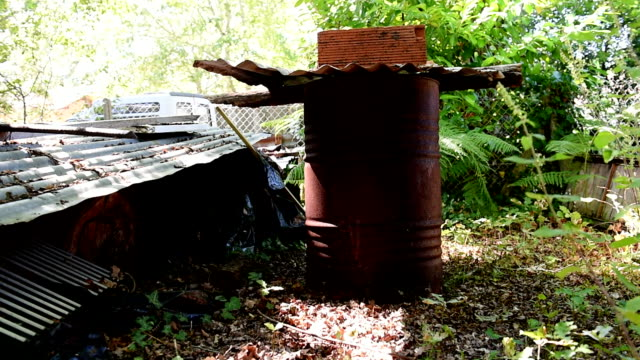 Rusty oil barrel and junk in a garden. Slide right to left. Long shot.