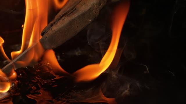 macro: pinng arruggino che tengono una lama metallica in olio durante la procedura di rinvenimento. - fabbro ferraio video stock e b–roll