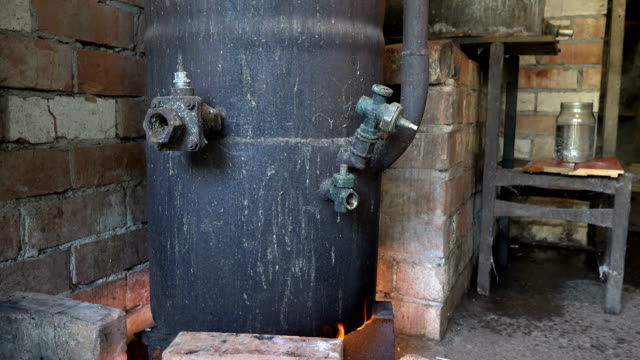 Rusty vodka distillation equipment on fire and hooch flow in jar video
