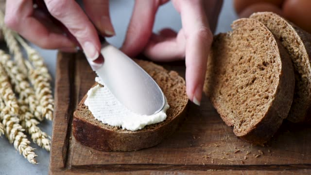 Rye bread with cream cheese Closeup view of spreading cream cheese on rye bread cheese stock videos & royalty-free footage