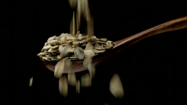 Rye flakes Rye flakes flows into wooden spoon rye grain stock videos & royalty-free footage