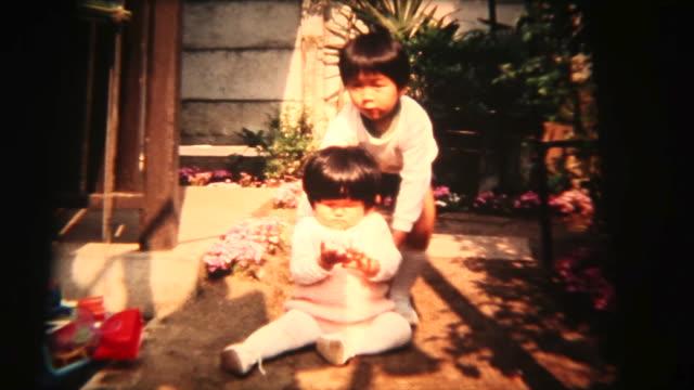 60 年代の 8 mm 映像-赤ちゃんの妹歩くに役立ちます - 兄弟姉妹点の映像素材/bロール