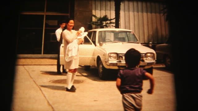 60 年代の 8 mm 映像 - 母と生まれたばかりの赤ちゃんを家に行く - アーカイブ画像点の映像素材/bロール