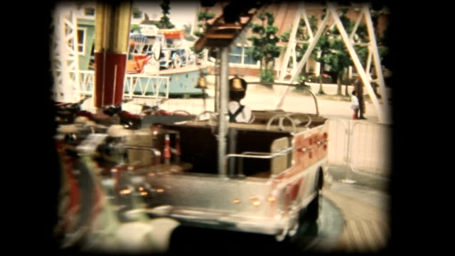 60's 8mm footage - young boy riding on a merry-go-round at amusement park. video