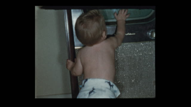1950's baby boy in diapers plays with antique television set - hotel reception filmów i materiałów b-roll
