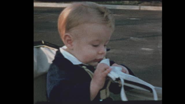 50's baby boy in stroller plays with mom's purse - hotel reception filmów i materiałów b-roll