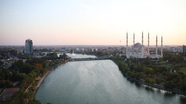 トルコの都市アダナにあるサバンチ中央モスク、オールドクロックタワー、ストーンブリッジ。セイハン川の前にモスクの小家があるアダナ市。 - モスク点の映像素材/bロール