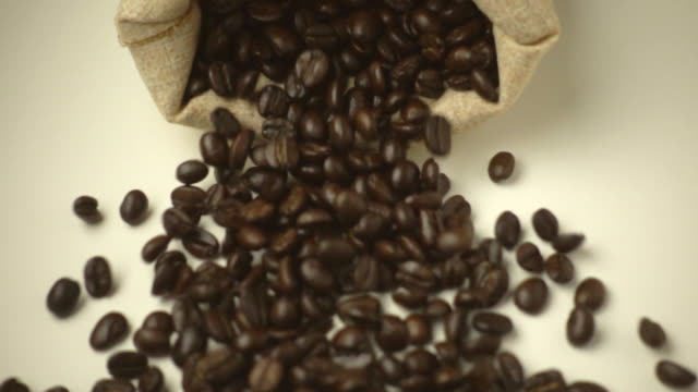 SLOW MOTION: Sac falls and a coffee beans fall out SLOW MOTION: Sac falls and a coffee beans fall out sac stock videos & royalty-free footage