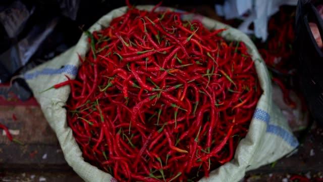 vídeos y material grabado en eventos de stock de saco de chilli pimientos rojos calientes en la cesta grande en el mercado tradicional - cayena guindilla roja