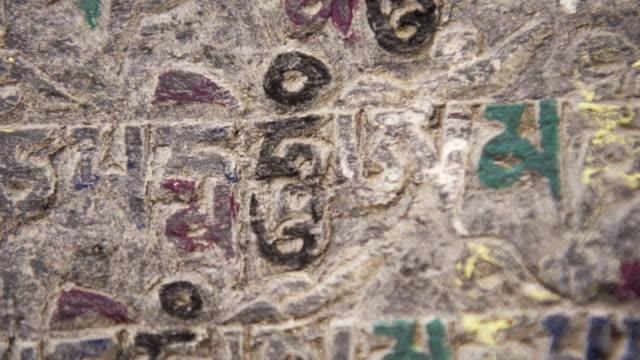 sacred buddhist text carved on stone - incisione oggetto creato dall'uomo video stock e b–roll