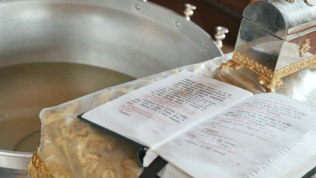 Sacred font with holy water, the bible with prayer at table in church video