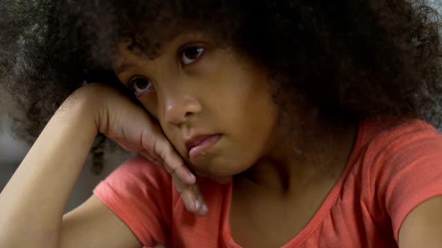 stockvideo's en b-roll-footage met triest afro-amerikaanse kind om thuis te zitten en te denken over haar eigen gedrag - acteur
