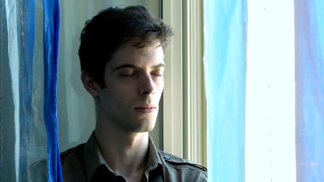 sad and anxious young man breathing near the window: pensive and worried - male eyes bildbanksvideor och videomaterial från bakom kulisserna