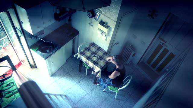 sad and depressed lonely tired woman is sitting in her kitchen: video