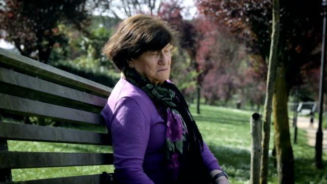 vídeos y material grabado en eventos de stock de mujer triste y deprimida en el banco del parque - memorial day