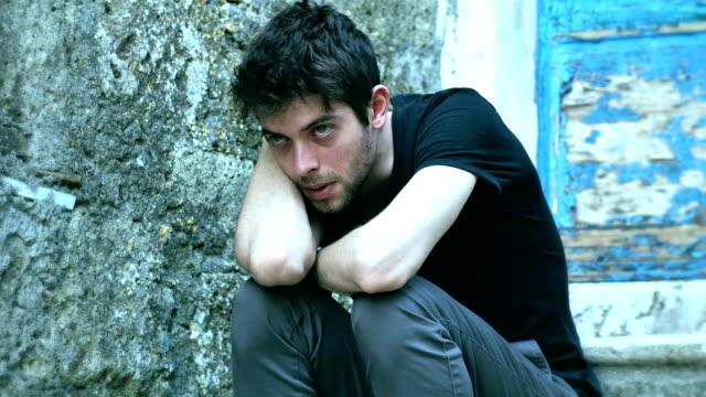 ledsen och deprimerad ung man sitter fundersam och ensam - male eyes bildbanksvideor och videomaterial från bakom kulisserna
