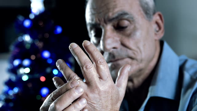 sad and lonely man remember his wife in the christmas time: depression, sadness old depressed man sitting alone and touching his wedding ring: he is remembering his dead wife. depression land feature stock videos & royalty-free footage