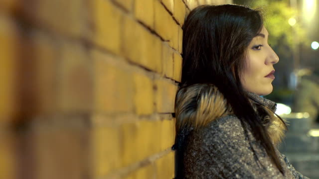 sad and pensive woman leaning against the wall video