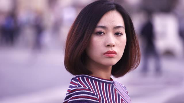vídeos de stock, filmes e b-roll de mulher chinesa triste e séria, vira a cabeça e olha para a câmera - virando