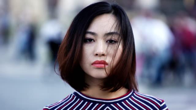 stockvideo's en b-roll-footage met droevige en ernstige chinese vrouw draait haar hoofd en kijkt naar de camera - portait background