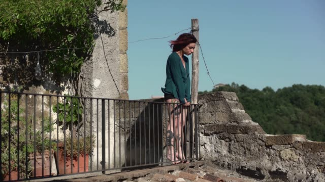 sad and thoughtful woman standing on the balustrade while the wind blows her hai - balaustrata video stock e b–roll
