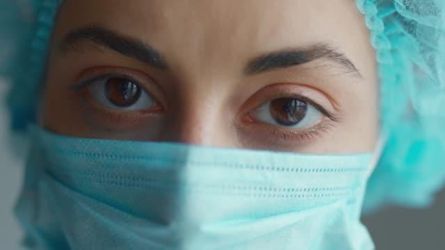 sad and tired medic opens eyes and looking atraight at camera