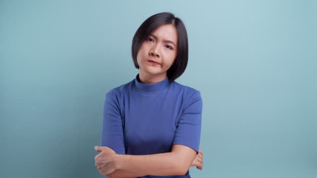 Sad asian woman looking at camera standing isolated on blue background. 4K video video