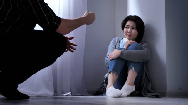 Sad Asian woman sits on the floor, angry husband threatens, conflict in the family, violence 50 fps