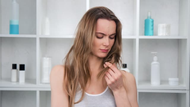 Sad attractive girl looking at unhealth hair ends having problem. Medium shot on RED camera Sad attractive girl looking at unhealth hair ends having problem and discomfort. Frustrated morning person touch dried tips needed haircare and repair procedure. Medium shot on RED camera human hair stock videos & royalty-free footage